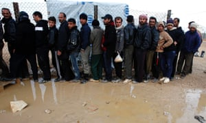 Syrian refugees queue for humanitarian aid at the Al Zaatri Syrian refugee camp in the Jordanian city of Mafraq, near the border with Syria.