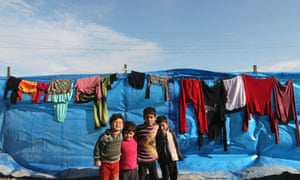 Young Syrian refugees stand in front of a tent at Bab al-Salam refugee camp in Azaz, near the Syrian-Turkish border. More than 600,000 Syrians have fled abroad.