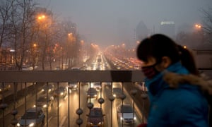 A smoggy day in Beijing as a woman wearing a mask walks over a road bridge.