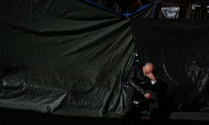In the black? A protester sits outside the headquarters of Spanish bank Bankia, at a campsite where protesters have demonstrated for some 100 days, in Madrid.