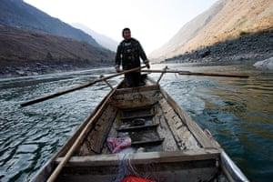 Yunnan Nujiang river: A fisherman sails his boat at the Nu River