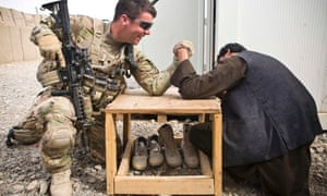 A U.S. army soldier and a member of the Afghan uniform police arm wrestle prior to a joint patrol near command outpost AJK (short for Azim-Jan-Kariz, a near-by village) in Maiwand District, Kandahar Province, Afghanistan.