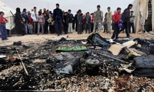 Syrian refugees look at remains of a burnt tent at Zaatari Syrian refugees camp, in Mafraq, near the Syrian border, Jordan, on Monday. A refugee tent caught on fire, and the family who lives in it was evacuated by the refugees.