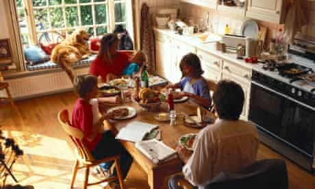 A family eating a meal in kitchen with a dog