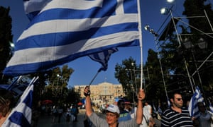 A woman holds a Greek flag in front of the parliament building in protest over the country's economic crisis.