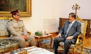 Abdel Fattah el-Sisi speaks to Egypt's president, Mohamed Morsi, at the presidential palace in Cairo.