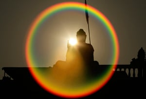 24 hours: A Buddha statue is silhouetted by the sun
