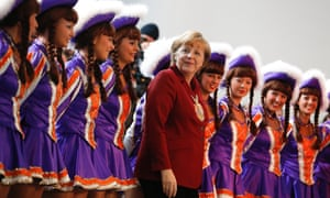 Today's Angela Merkel picture sees the German chancellor poses for pictures with a dance troupe during a reception of German carnival societies at the Chancellery in Berlin.