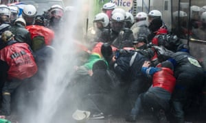 Steel workers from the ArcelorMittal plant in Liege, take cover as police use a water cannon during a protest near the Walloon minister president's office in Namur, Belgium. The world's leading steel and mining company ArcelorMittal announced last week it will close a coke plant and six production lines in Belgium, in a move that threatens 1300 jobs.
