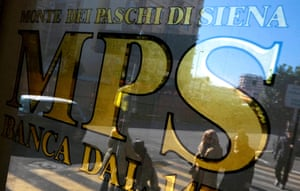 People are reflected in the window of a Monte Dei Paschi Di Siena bank in Rome January 29, 2013.