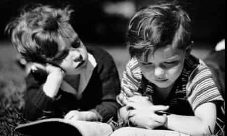 Two boys reading outdoors circa 1950s