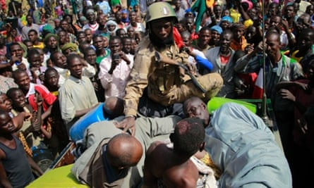 A Malian soldier rounds up suspected Islamist extremists in Gao, northern Mali. Four suspects were arrested after being found by a youth militia calling themselves the 'Gao Patrolmen'. Their capture by the army prevented them from being lynched by a mob.