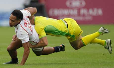 United States player Maka Unufe, left, is tackled by Australia's Cameron Clark at the Dubai Sevens