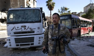 Japanese trucker Toshifumi Fujimoto holds his cameras in front of damaged buses in Aleppo's old city.