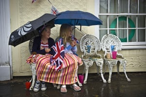Wet UK weather 2012 : June: Spectators sheltering from rain as they wait for the Olympic Flame