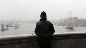 Wet UK weather 2012 : June: A policeman looks out over the River Thames