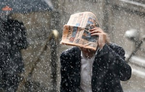Wet UK weather 2012 : April: A man tries to shelter under a copy of the Financial Times