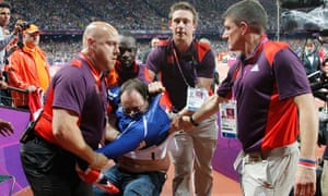 A man is detained by security shortly after an incident at the start of the men's 100m final