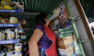 A woman fixes a poster of Hugo Chavez
