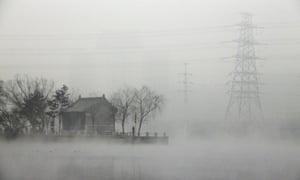 A man fishes near a temple beside a river on a heavy hazy day in Beijing's Gaobeidian village, China. Beijing has temporarily shut down over a hundred heavily polluting factories to combat dangerously high air pollution.