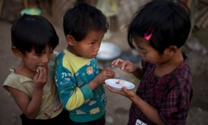 Children eat dates after dipping them in a small plate with salt at refugee camp in northern Burma's Kachin-controlled region.
