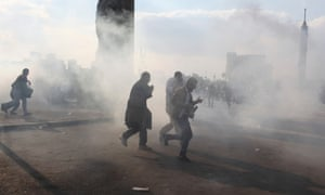Protesters walk away from tear gas fired by riot police during clashes on Qasr el-Nil bridge, in Cairo.