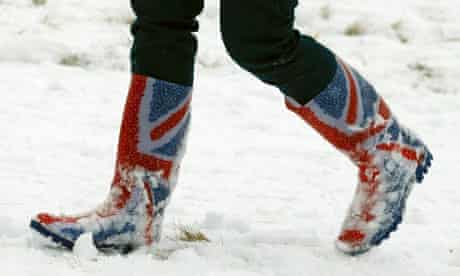 A woman walks through snow in Wellington boots printed with the union flag