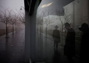 24 hours in pictures: Ultra Orthodox Jewish men stand at a train station
