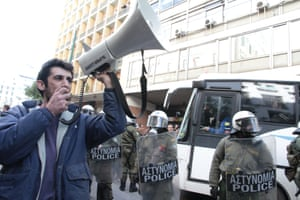 A man shouts on a megaphone next to the police. Various Greek workers along with Union members occupied the ministry of Labour, before being arrested and prosecuted by Greek police.