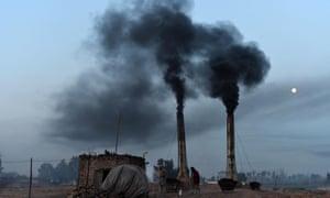 Labourers work as smoke rises from a brick kiln in Peshawar, Pakistan.