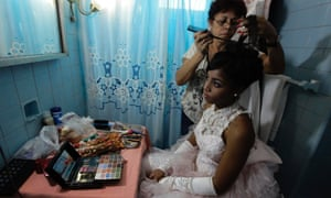 Carmen Gonzalez has her hair done for her quinceanera (coming-out for 15-year-olds) celebration, in Havana, Cuba. The quinceanera is very popular and the industry surrounding it is large.
