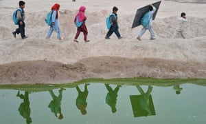Afghan schoolchildren walk  home after classes in an open classroom on the outskirts of Jalalabad.