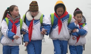 Students walk arm in arm to prevent from slipping at Beijing Olympic park, after freezing rain on another smoggy day in Beijing.