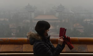 A Chinese tourist takes photos from the historic Jingshan Park as smog continues to shroud Beijing. Hospital admissions for respiratory complaints rose in recent days