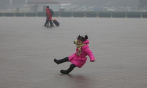 A girl slips on the icy ground at the Tiananmen Square during severe pollution.