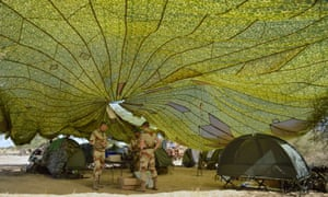 French Foreign Legion troops work under a deployed parachute at Timbuktu airport after returning from northern Malian desert city.