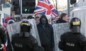 Police in riot gear try to contain loyalist protesters during clashes in Belfast over the union flag