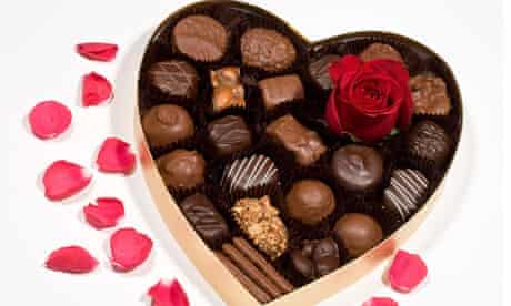 Valentine's red rose in heart shaped box of chocolates