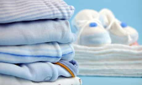 Pile of blue baby clothes and slippers on cotton diapers