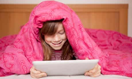 Girl playing ipad in bed