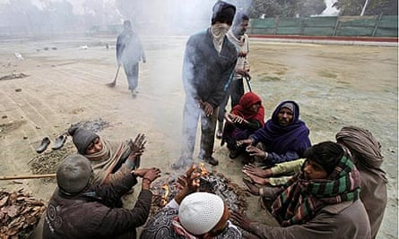 Municipal workers in Delhi warm themselves around a bonfire