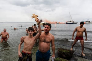 Epiphany Day: A youth holds up a cross after retrieving it from the water