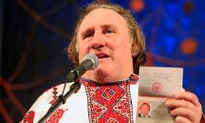 Gerard Depardieu, wearing a local costume, shows his passport