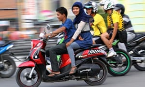 An Acehnese woman straddles a motorbike
