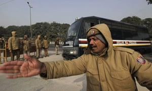 A Delhi policeman clears the way for a police van