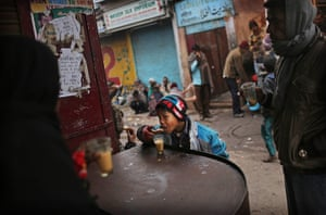 Cold weather in India: A young Indian boy eats a biscuit with his tea