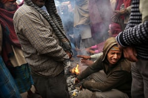 Cold weather in India: Labourers warm themselves on a fire in a market in New Delhi