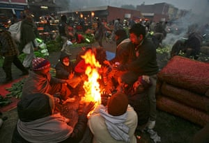 Cold weather in India: People warm themselves by a fire at a vegetable wholesale market