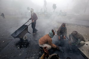Cold weather in India: Labourers repair a road surrounded by fog  in Allahabad