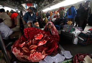 Cold weather in India: Passengers wrap themselves in a blanket as they wait to board a train